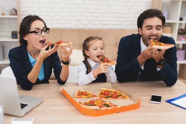 The whole family eats pizza at home with pleasure.