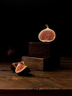 Whole figs and one fig cut in half on a wooden table