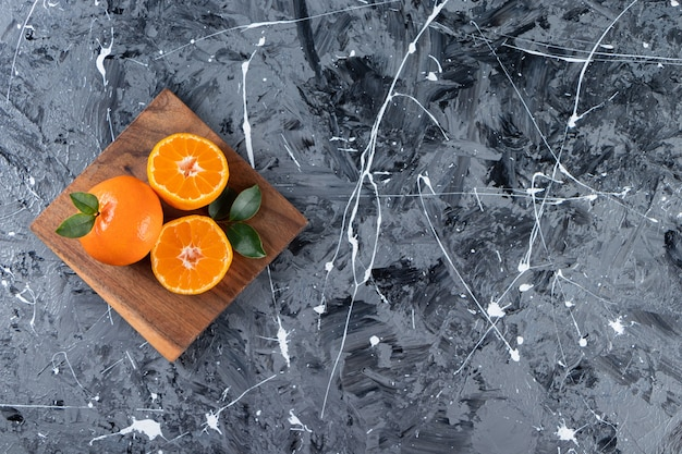 Whole fresh orange fruits with leaves placed in a board.