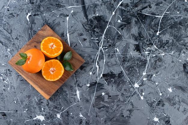 Frutti interi di arancia fresca con foglie poste in una tavola.