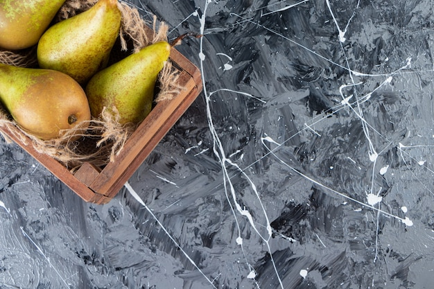 Целые свежие груши в деревянной старой коробке на мраморном столе.