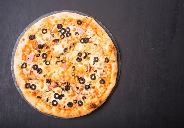 Whole fresh pizza with olives and meat topping on slate over dark backdrop