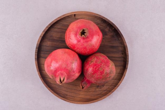 Whole fresh pomegranates on wooden plate.