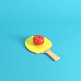Whole fresh red tomato with water drops on ping pong paddle with yellow rubber isolated on blue background
