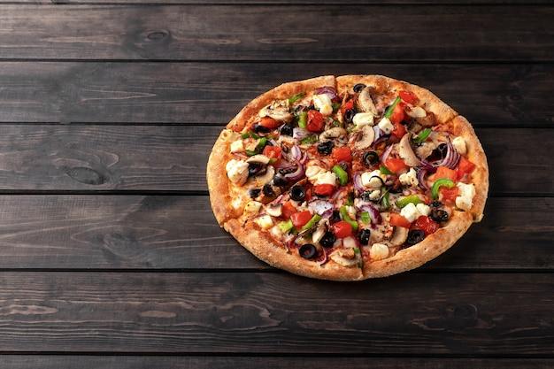 木製の茶色のテーブルに鶏肉、野菜、きのこ、チーズのクローズアップを添えた新鮮な丸いピザ。コピースペースのあるピッツェリアのおいしいファーストフードの表面