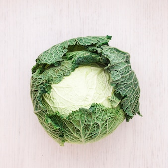 Whole fresh savoy cabbage on wooden surface