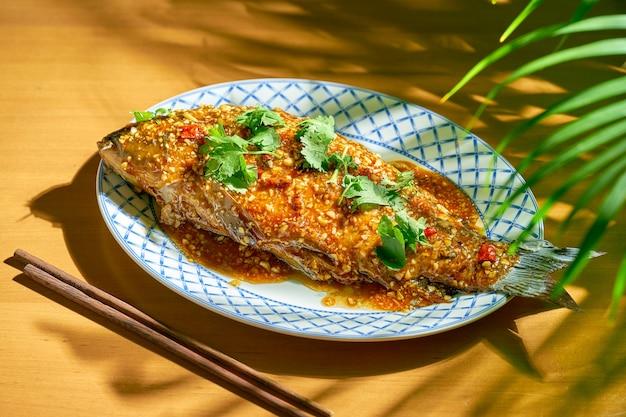鯉の炒め物にホットソースと花椒を添えて。木の背景。中華料理