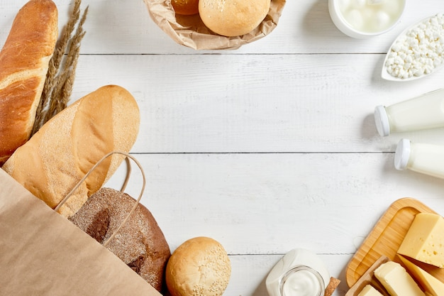Whole grain bread in ecology paper bag on white wooden background. flat lay.natural organic food: milk, cheese, sour cream and bakery. save ecology concept. zero waste recycling. copy space.