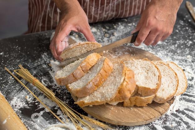 穀物のパンは、カットのためのナイフを保持するシェフとキッチンの木製のプレートに置く。テーブルの上に新鮮なパン。