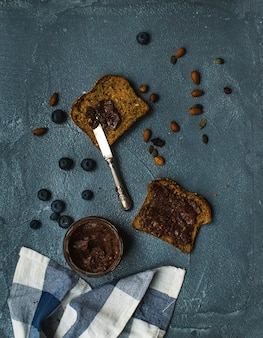 Whole grain bread toasts with organic vegan chocolate peanut butter, blueberry, nuts over grunge grey table