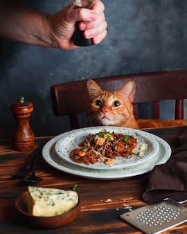 バジル、ニンニク、ブリーチーズの全粒そばパスタ。男性はペッパーシェーカーを保持します。赤い猫は木製キッチンテーブルの前に茶色の椅子に座っています。