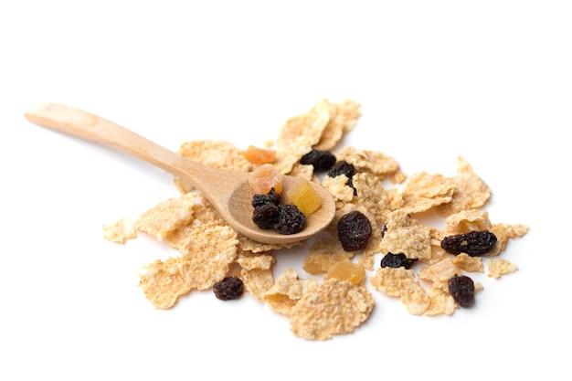 朝食にベリーフルーツとレーズンを混ぜた全粒穀物フレークが白い背景に分離されました