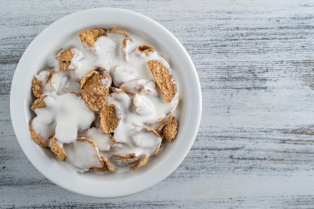 Цельнозерновые глазированные хлопья с йогуртом в тарелке, крупным планом, вид сверху. здоровый завтрак, цельнозерновые мюсли в миске