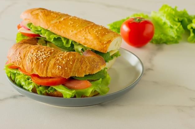 양상추, 아보카도, 토마토, 치즈를 곁들인 통곡물 롱 바게트 비건 샌드위치. 건강에 좋은 간식과 먹을거리.