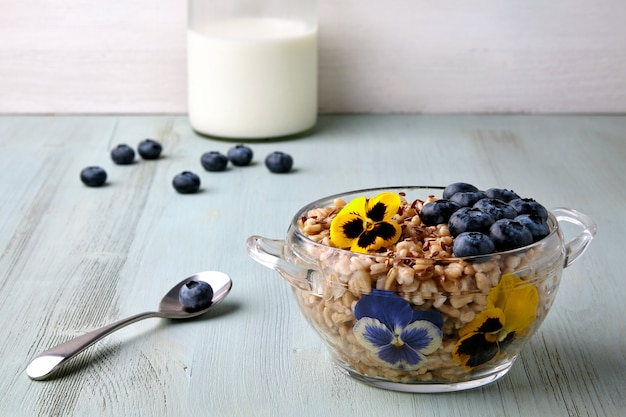 Whole grain oatmeal in a glass bowl with blueberry