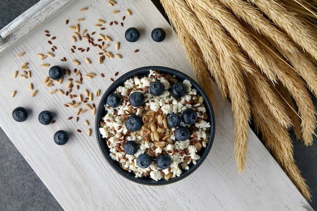 Whole grain oatmeal porridge with flax seeds, blueberries, cottage cheese and ears of wheat on a white painted wooden tray