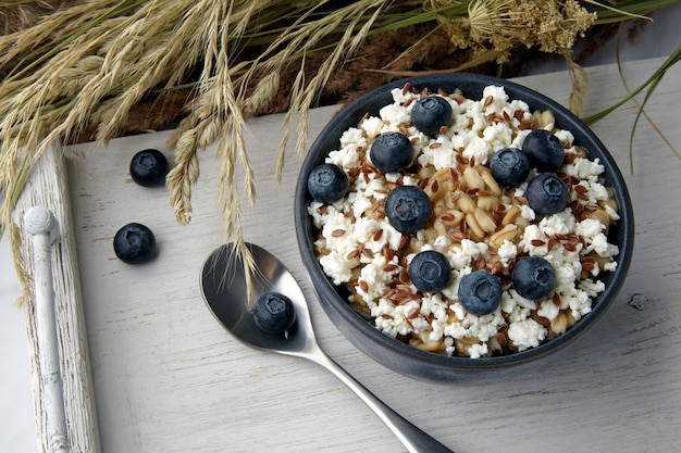 Whole grain oatmeal porridge with flax seeds and blueberries on a white vintage serving with a bouquet of dry herbs