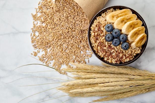 白い大理石のテーブルの上に散らばった穀物、トウモロコシの穂に囲まれた、暗いボウルにブルーベリーとバナナのスライスが入った全粒オートミール。エネルギーのための朝食
