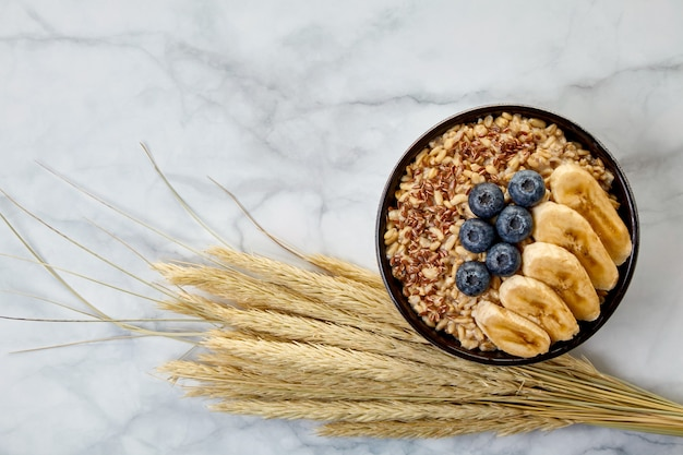 Whole grain oatmeal with blueberries and banana slices in a dark bowl, surrounded by sprinkled grains, ears of corn. international porridge day