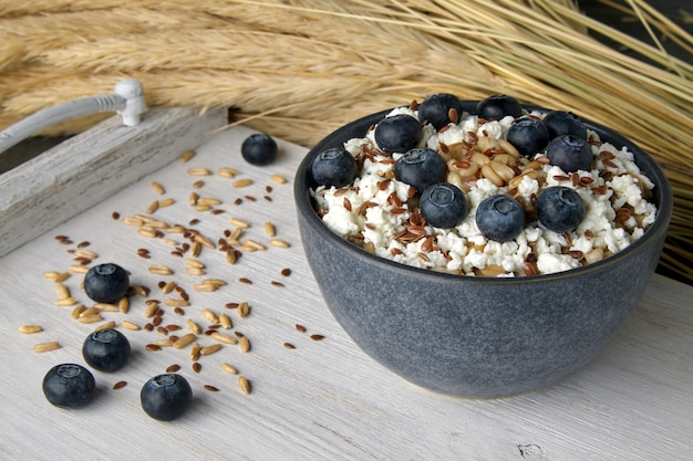 Whole grain oatmeal with blueberries, flax seeds and cottage cheese on a vintage dyed rack surrounded by a sheaf of ears