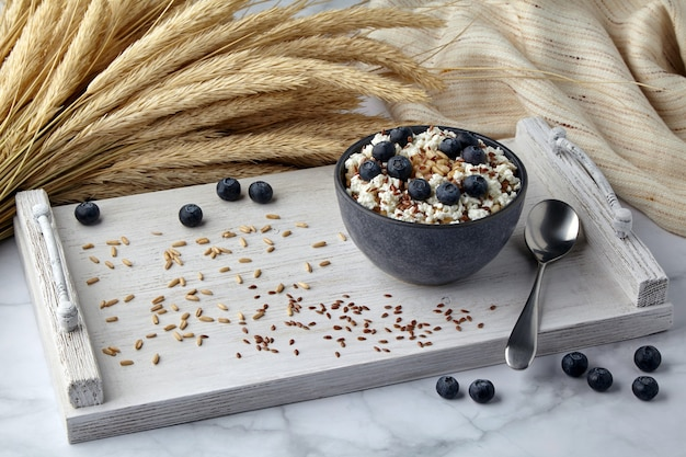 Whole grain oatmeal with blueberries, flax seeds and cottage cheese on a white painted tray surrounded by ears of corn and a tea towel