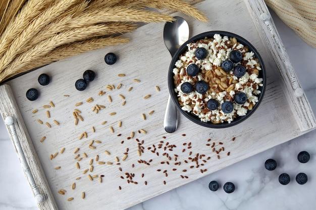 プロヴァンススタイルの木製トレイにブルーベリーカードと亜麻の種子とトウモロコシの穂が付いた全粒オートミール。エネルギーのための朝食