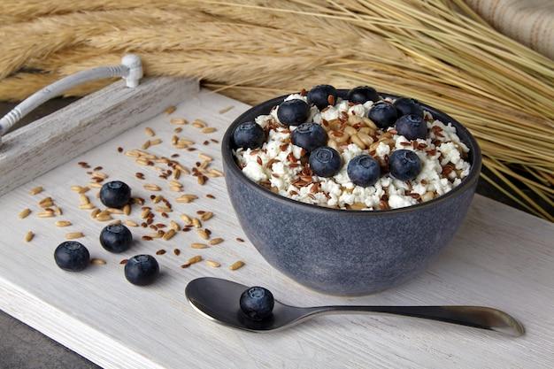 白く塗られた木製のトレイにブルーベリーカードと亜麻の種子と小麦の穂が付いた全粒オートミール。ビーガン食