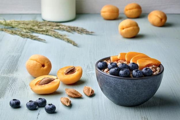 Цельнозерновая овсяная каша с семенами льна, кусочками абрикоса и черникой на синем деревянном столе в окружении ингредиентов. здоровый завтрак для энергии