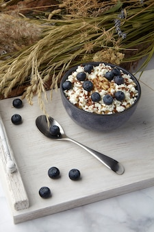 Whole grain oatmeal with flax seeds and blueberries on white vintage serving with dry herbs bouquet