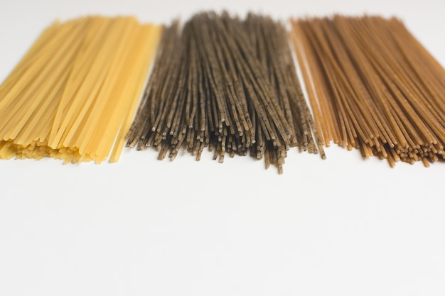 Whole-grain pasta spaghetti tricolora on a white background