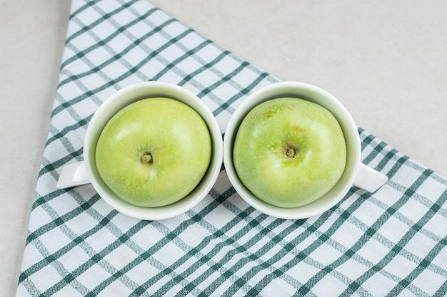 テーブルクロスと白いカップの全体の青リンゴ