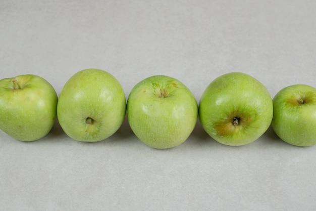 회색 표면에 전체 녹색 사과