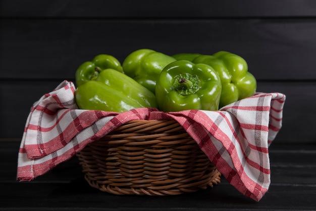 Peperoni dolci verdi interi posti sulla tavola di legno scuro. foto di alta qualità