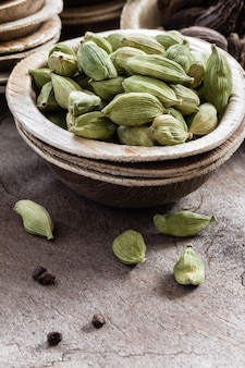Whole green cardamom in a bowl on wood
