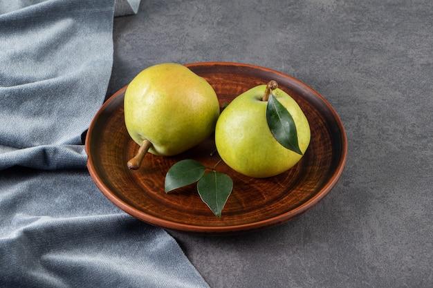 石のテーブルの上に置かれた丸ごとの緑の梨。