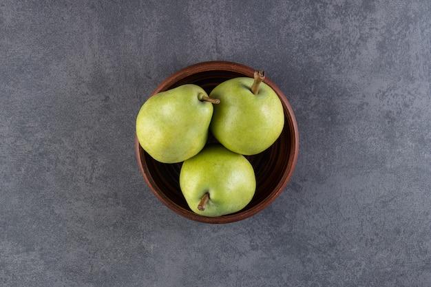 木製のボウルに置かれた丸ごとの緑の梨。