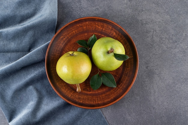 Whole green pears placed on a stone table.