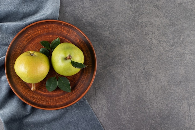 Pere verdi intere poste su un tavolo di pietra.