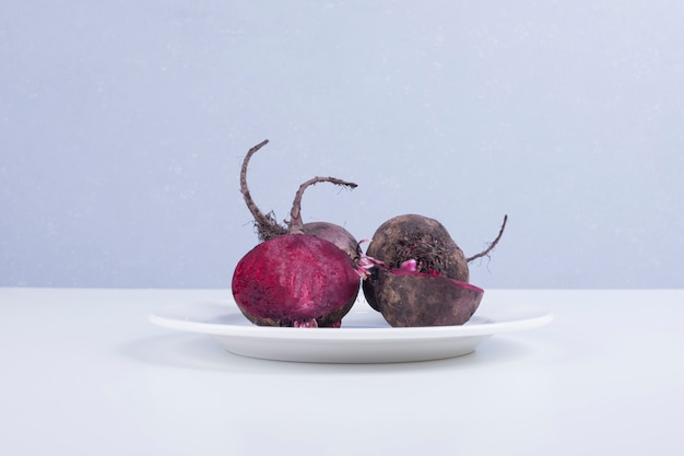 Whole and half beetroots in a white plate on blue.