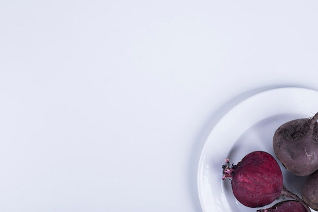 Whole and half beetroots in a white plate on right corner