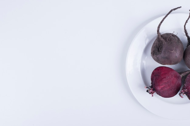 Whole and half beetroots in a white plate on right side.