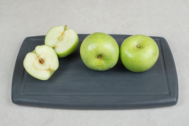 Whole and half cut green apples on dark plate