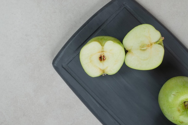 Mele verdi intere e tagliate a metà sul piatto scuro