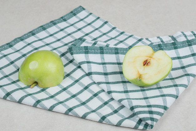 Whole and half cut green apples on tablecloth