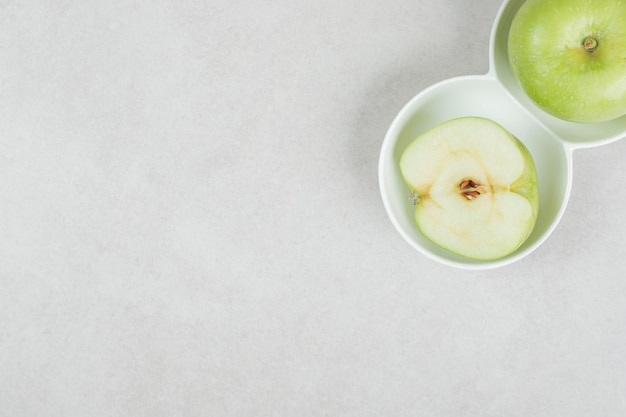 Whole and half cut green apples in white bowls