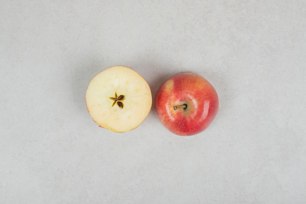 Whole and half cut red apple on gray surface.