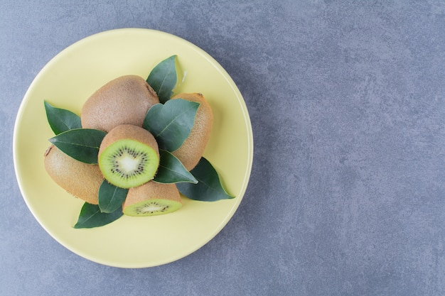 Whole and half kiwi fruits on plate on the dark surface