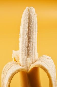 Целая половина очищенного банана, изолированного на желтом