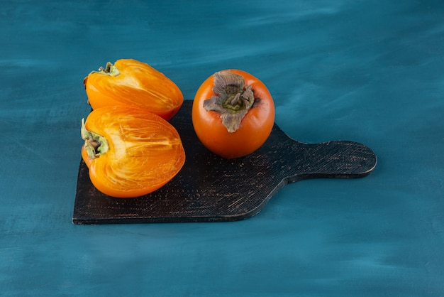 Whole and half sliced persimmon fruits on black cutting board.