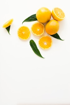 An whole and halved oranges with green leaves isolated on white background